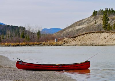 empty canoe sitting on the shore