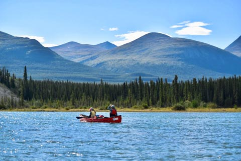 Parent and cild paddling on river on clear day with mountain and forest in back ground