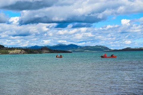 2 canoes with paddlers on a big lake with mountains